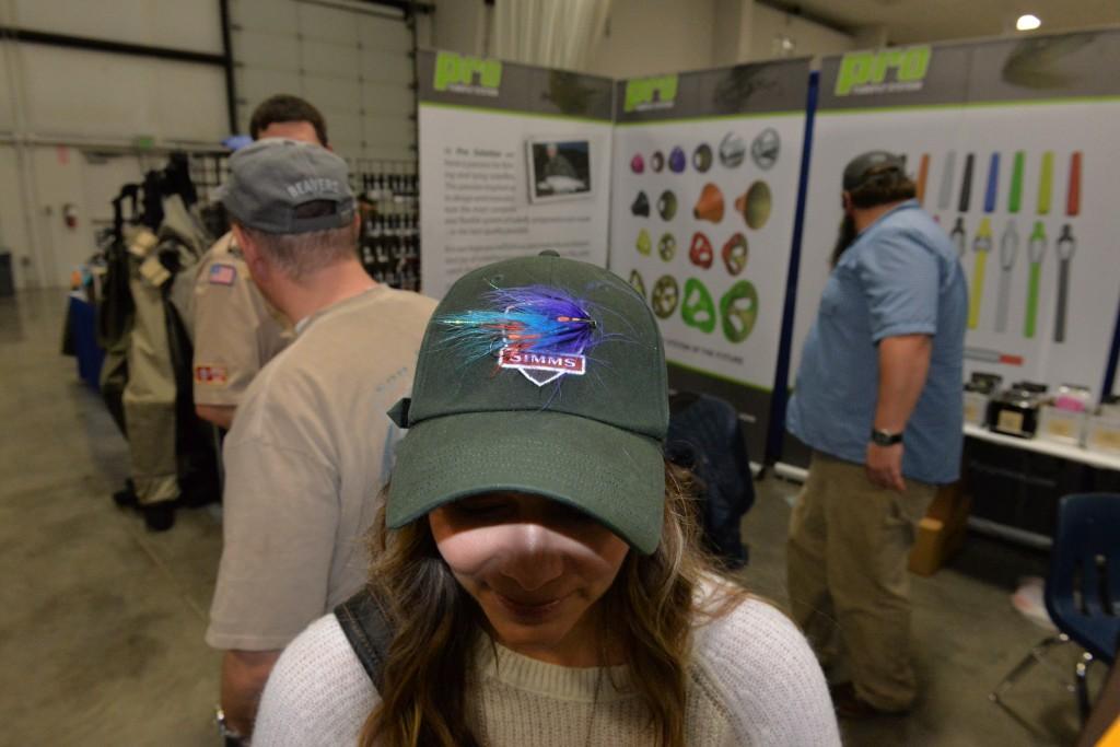 Lisa with steelhead fly in SIMMS ball cap.